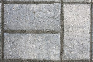 Closeup of three paver bricks in a paved stone patio floor.